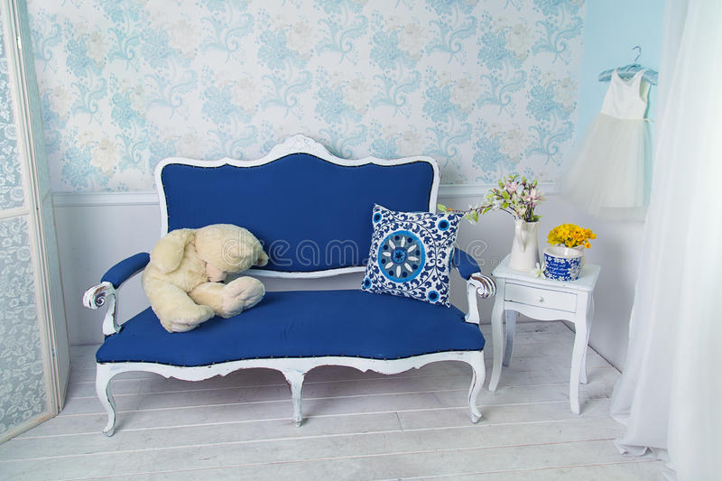 Blue classical style sofa couch with white teddy bear stock photos