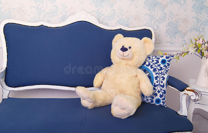 Blue classical style sofa couch with white teddy bear royalty free stock photos