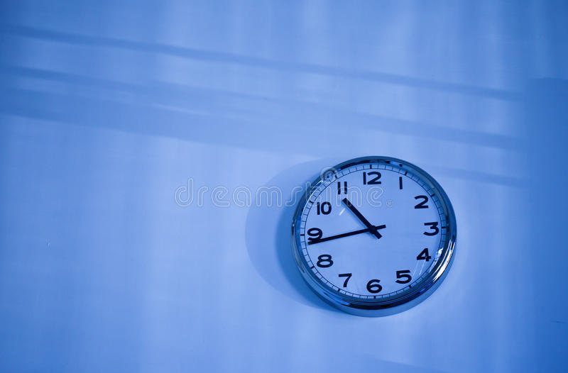 Download Blue clock on a blue wall stock photo. Image of business - 28282008