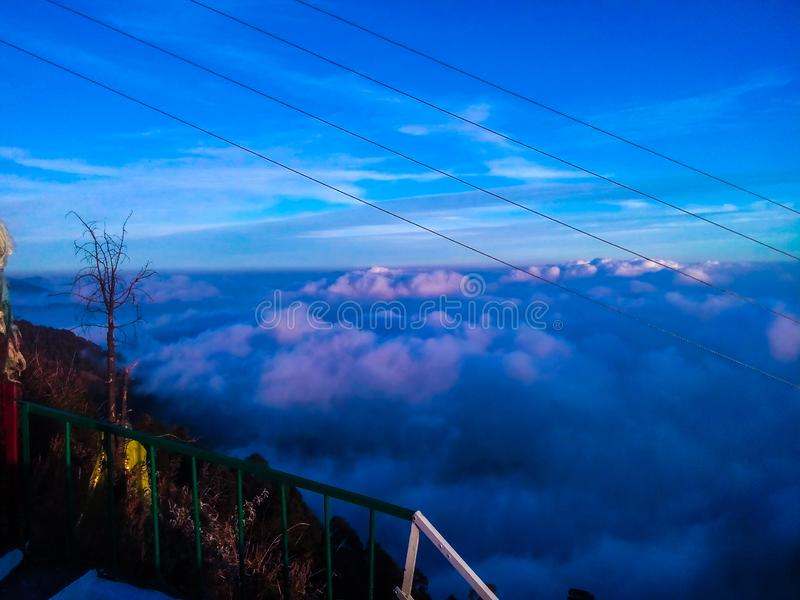Blue clouds over mountains in evening shadow stock image