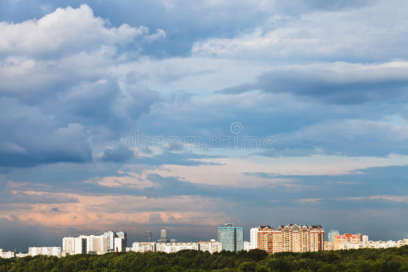 Blue clouds in pink sky over town stock photography
