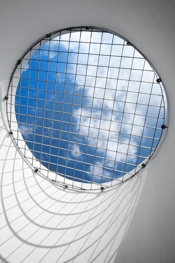 Blue cloudy sky behind the round window with metal grid royalty free stock photography