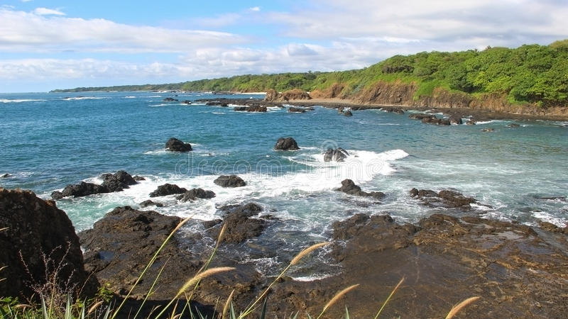 blue cloudy sky and crashing waves on a exotic isolated beach in costa rica, volcanic rocks and turquoise water stock images