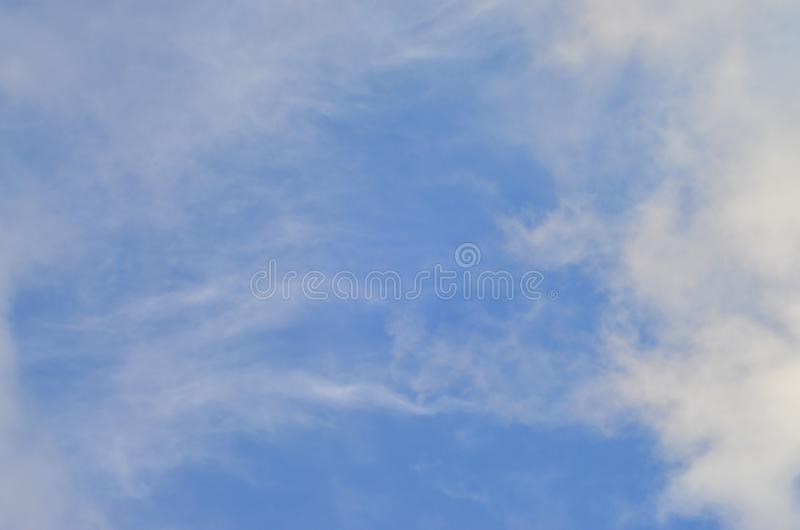 A blue cloudy sky with many small clouds blocking the su. N royalty free stock images