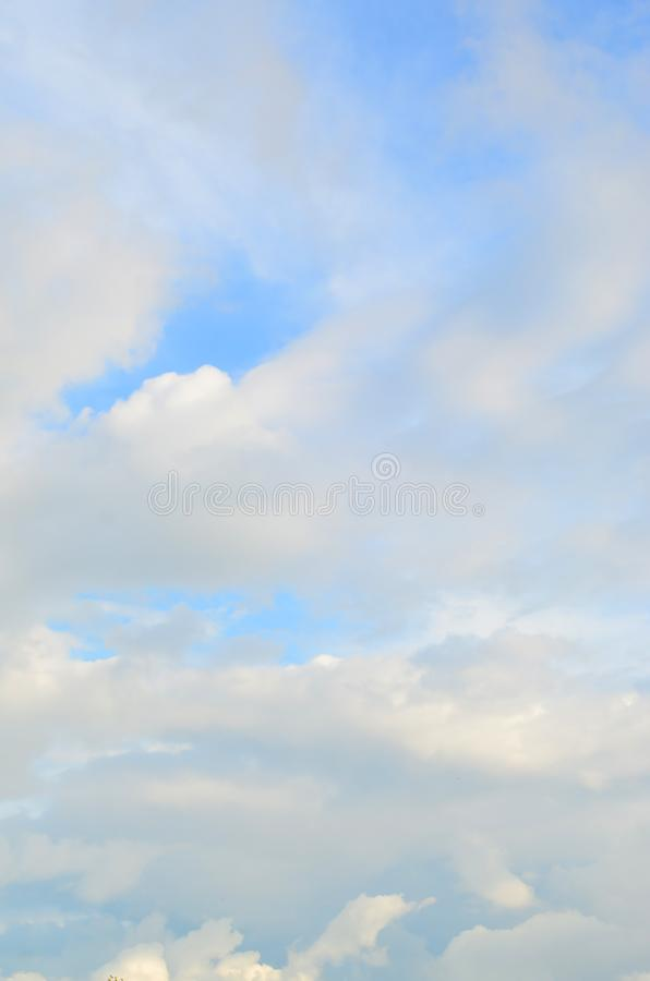 A blue cloudy sky with many small clouds blocking the su royalty free stock photo