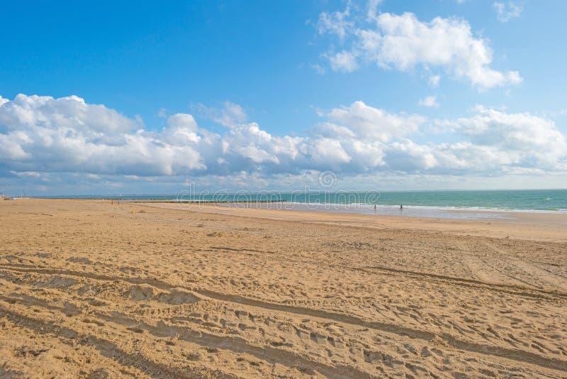 Blue cloudy sky over a sand beach along the sea stock photo