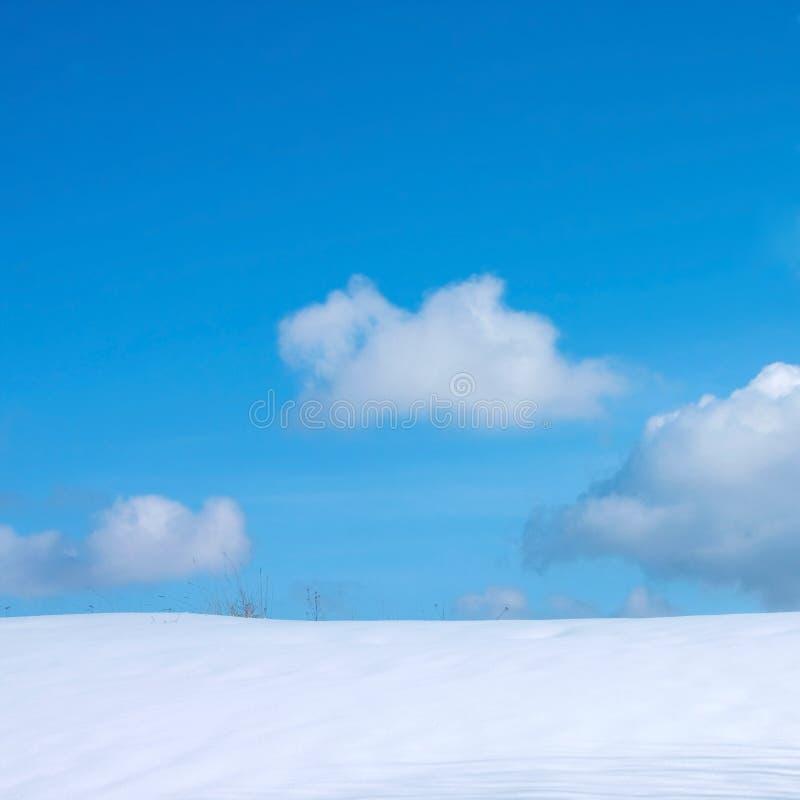 Blue cloudy sky and snow stock photos