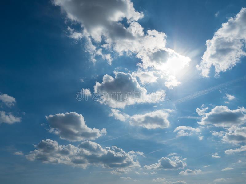 Blue and cloudy sky on a sunny day stock image