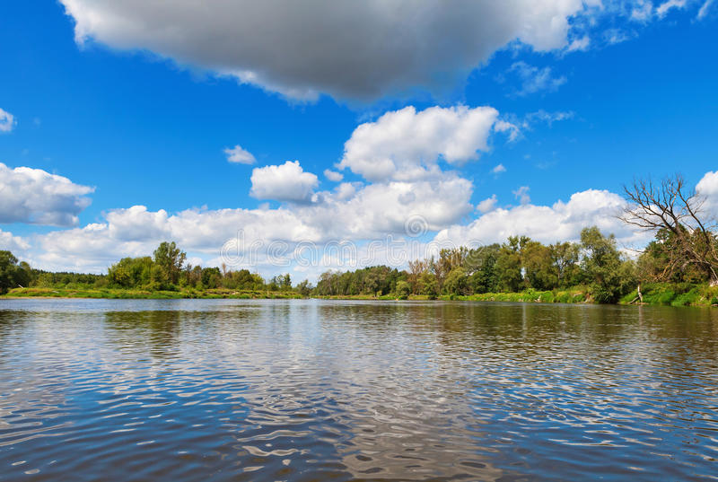Blue cloudy summer sky over Bug river stock photography