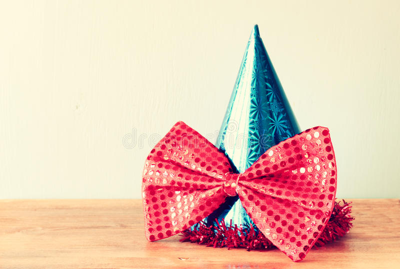 Blue clown hat and big bow tie over wooden table royalty free stock image