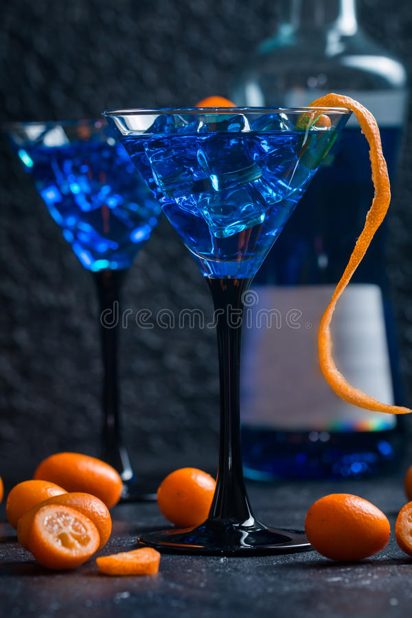 Blue cocktail in martini glasses. With ice and Kumquat on black background royalty free stock photos