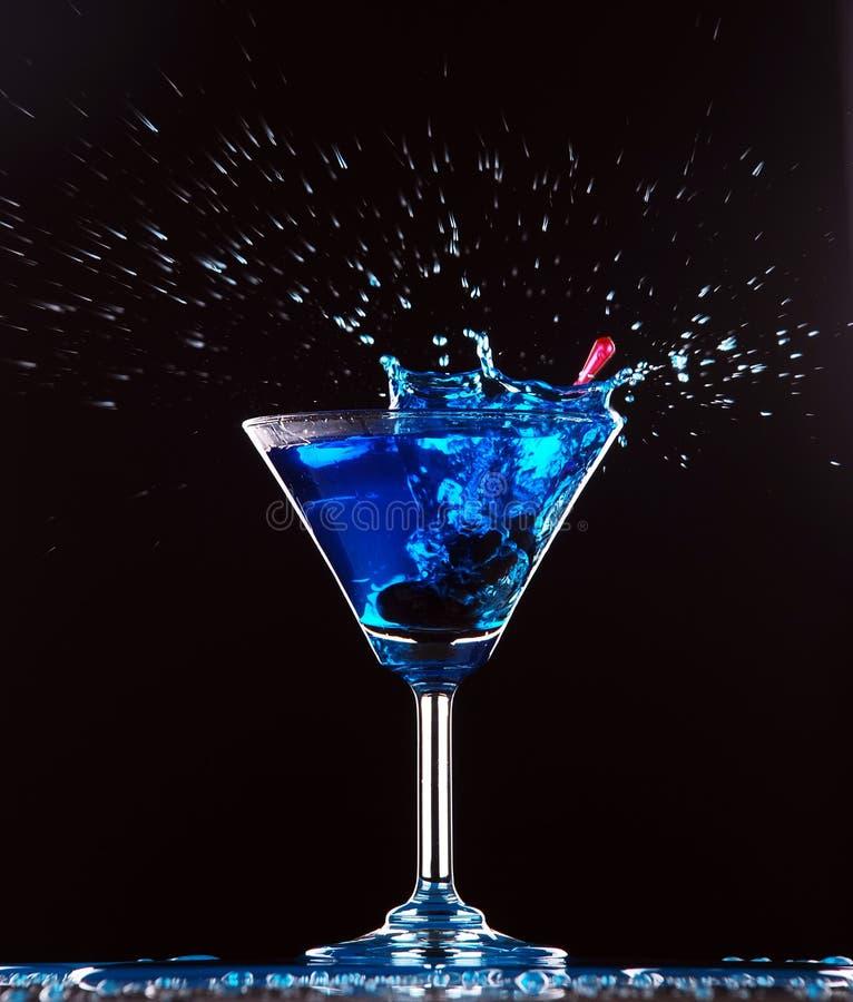 Blue cocktail splashing. On dark background stock photos