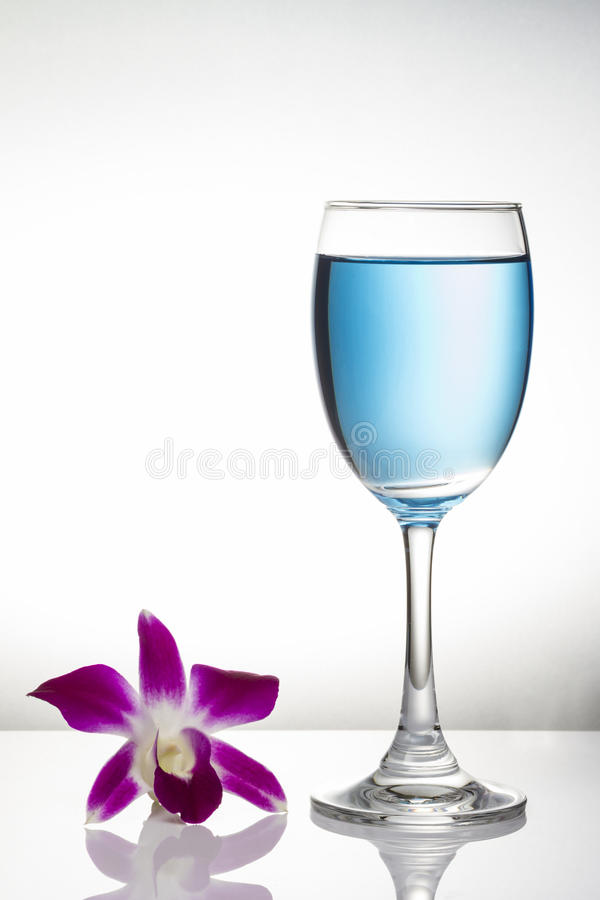 Blue cocktail in wine glass and orchid flower on white background stock image