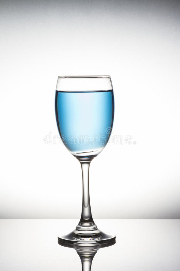 Blue cocktail in wine glass on white background royalty free stock photo