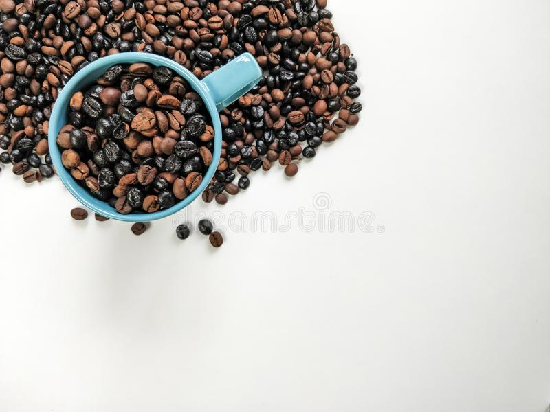 Blue coffee cup with coffee beans surrounding, with blank space for advertisement. Top view. Blue coffee cup with coffee beans surrounding, with white space for stock images