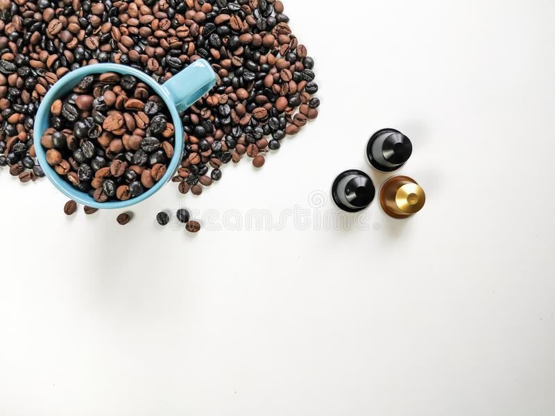 Blue coffee cup, with coffee beans surrounding, three coffee capsules, with white background. Top view.  stock photo