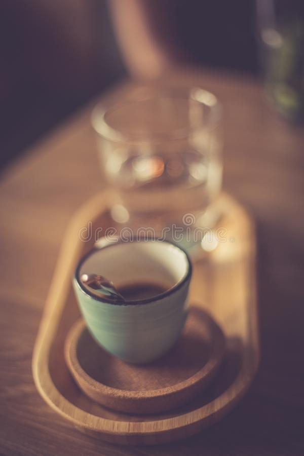 A blue coffee cup with black coffee. On a wood table, in a coffeeshop stock images