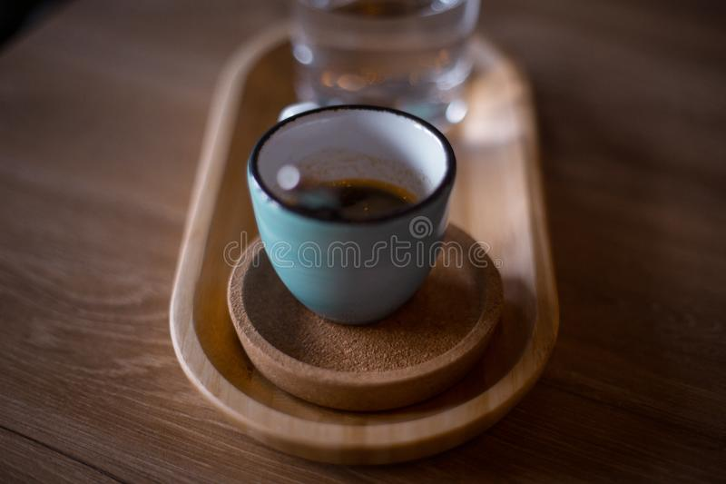 A blue coffee cup with black coffee. On a wood table, in a coffeeshop royalty free stock photography