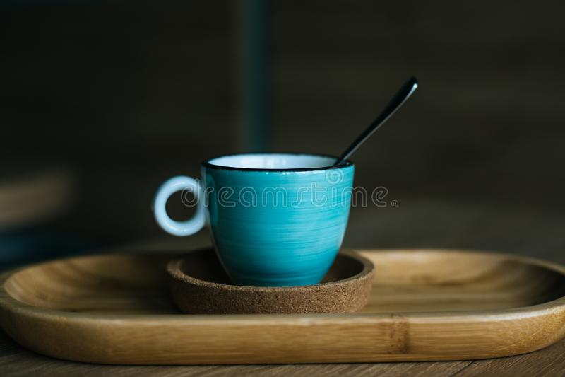 A blue coffee cup with black coffee. On a wood table, in a coffeeshop royalty free stock images
