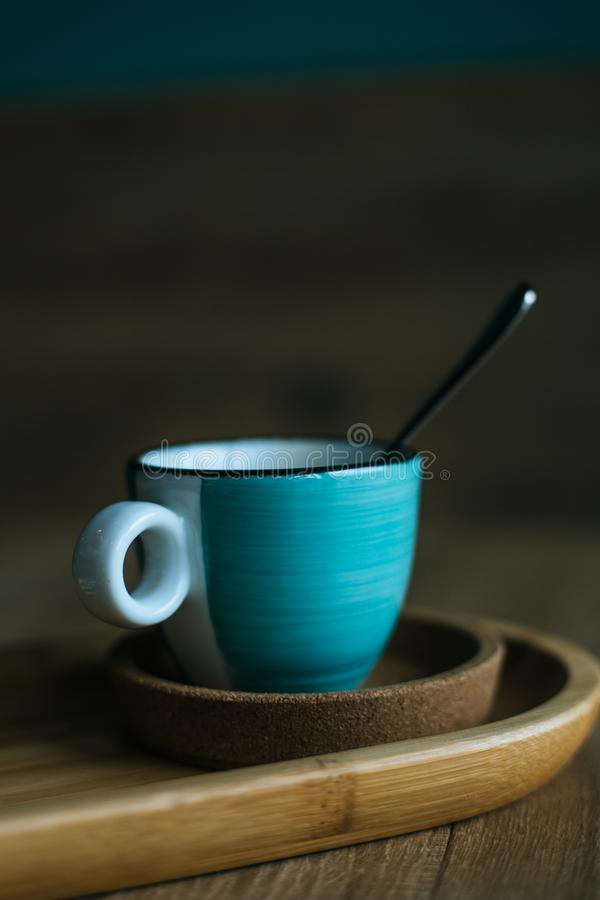 A blue coffee cup with black coffee. On a wood table, in a coffeeshop stock photography