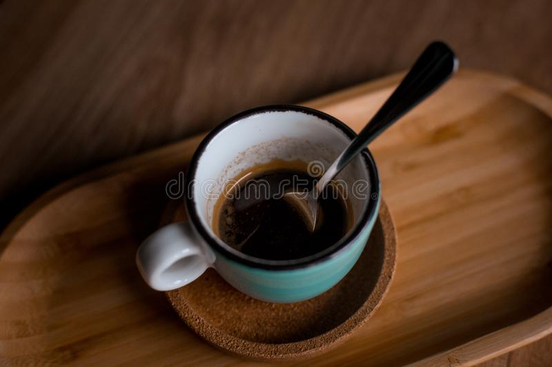 A blue coffee cup with black coffee. On a wood table, in a coffeeshop royalty free stock photos