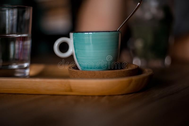 A blue coffee cup with black coffee. On a wood table, in a coffeeshop stock image