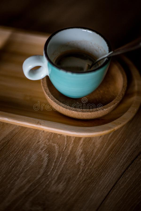A blue coffee cup with black coffee. On a wood table, in a coffeeshop stock photos
