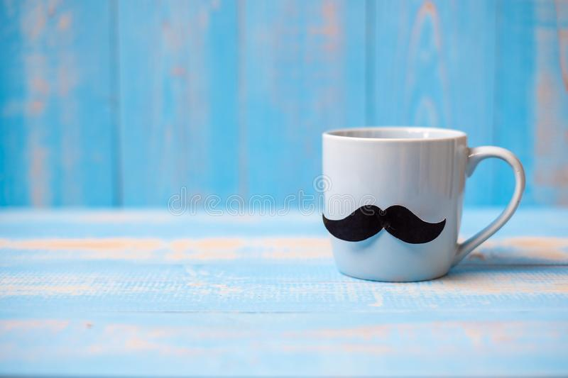 Blue coffee cup with Black mustache on wood table background in the morning. Father, International men day, Prostate Cancer stock image