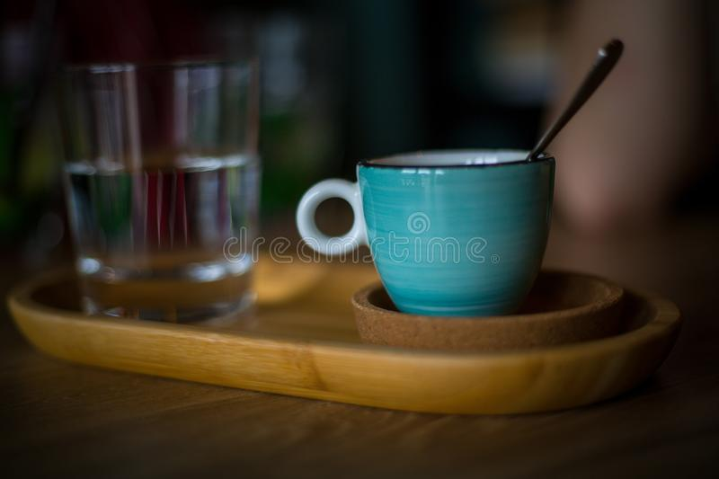 A blue coffee cup with black coffee. On a wood table, in a coffeeshop royalty free stock image
