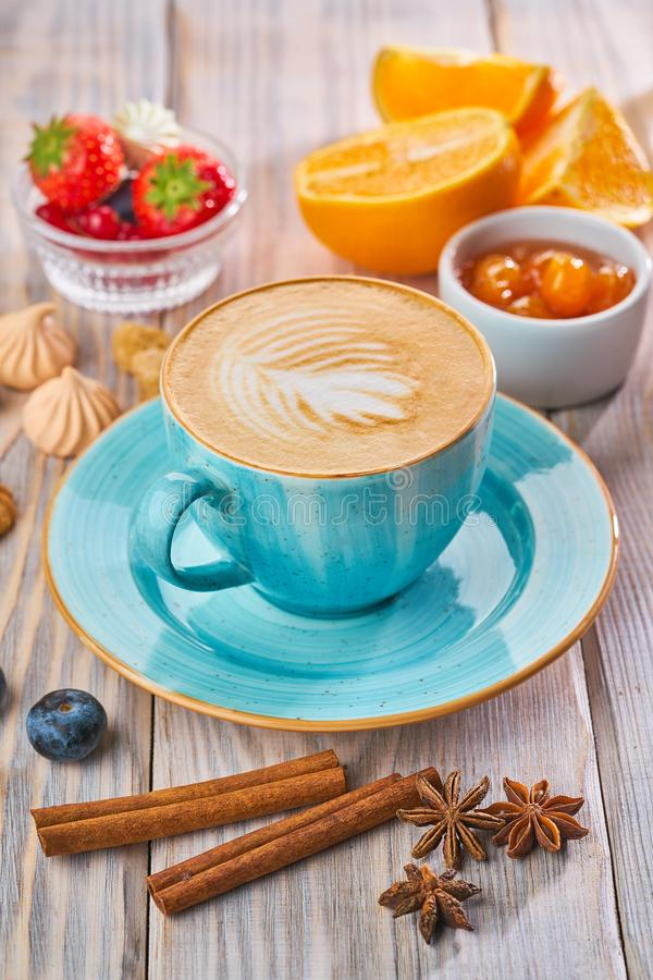 Blue coffee cup with cappuccino, cinnamon and anise. Breakfast concept. Blue coffee cup with cappuccino, cinnamon and anise royalty free stock photography