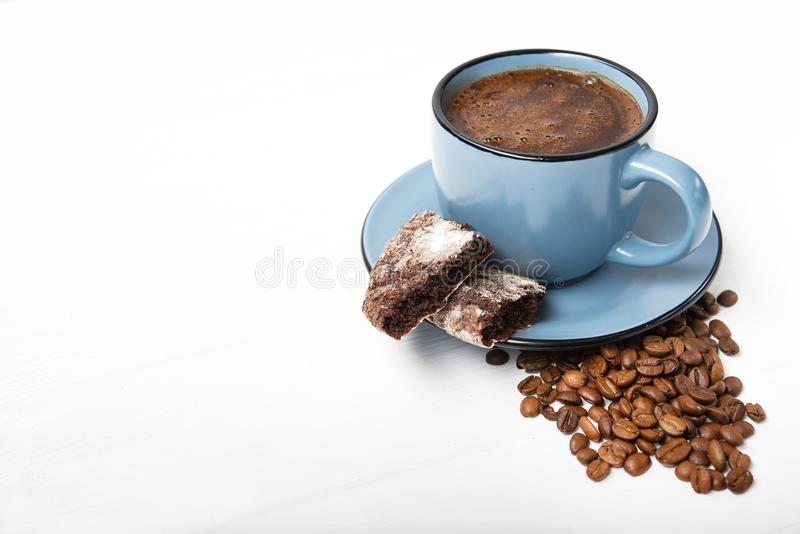 Blue coffee cup with chocolate cookie. On a white wooden table royalty free stock photos
