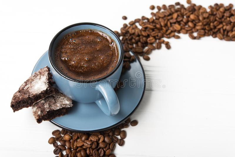 Blue coffee cup with chocolate cookie. On a white wooden table stock photography