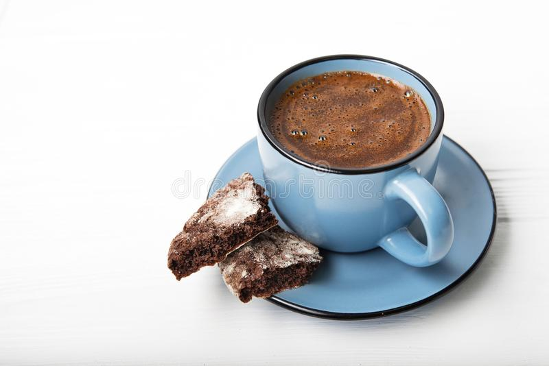 Blue coffee cup with chocolate cookie. On a white wooden table royalty free stock image