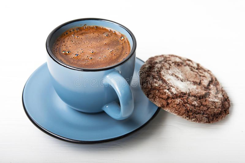 Blue coffee cup with chocolate cookie. On a white wooden table stock image