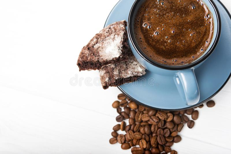 Blue coffee cup with chocolate cookie. On a white wooden table stock photos