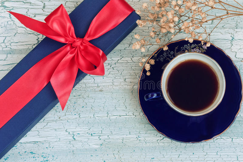 Blue coffee cup and gift box on wooden table, rustic style. Blue coffee cup, gift box and small flowers on wooden table, rustic style stock image