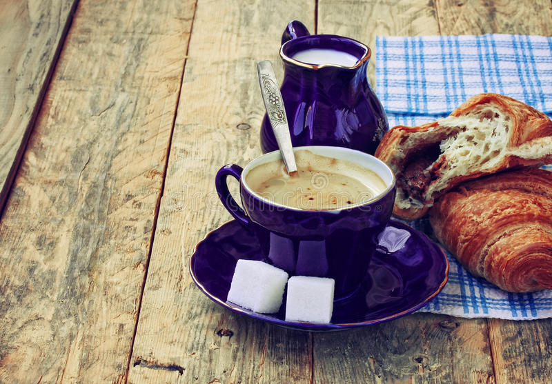 Blue coffee cup, milk jug and croissant with chocolate filling. Blue coffee cup, milk jug with milk and croissant with chocolate filling, on wooden table, rustic royalty free stock photo