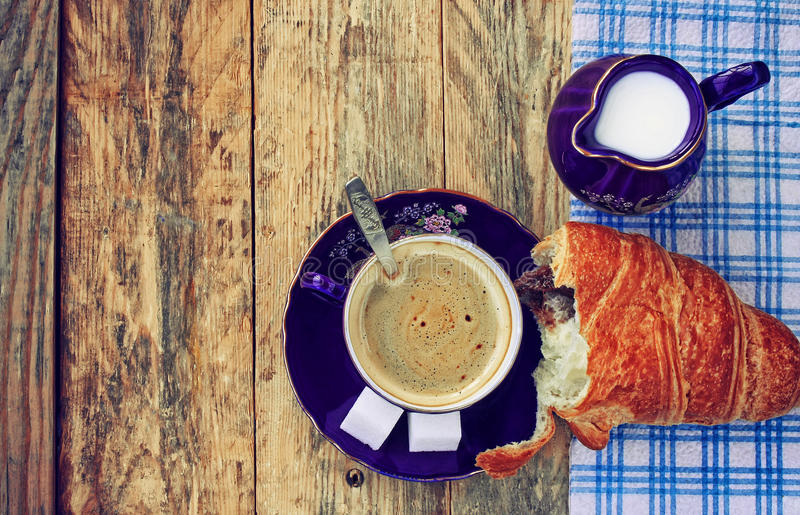 Blue coffee cup, milk jug, top view. Blue coffee cup, milk jug with milk and croissant on a wooden table, rustic style, top view stock images