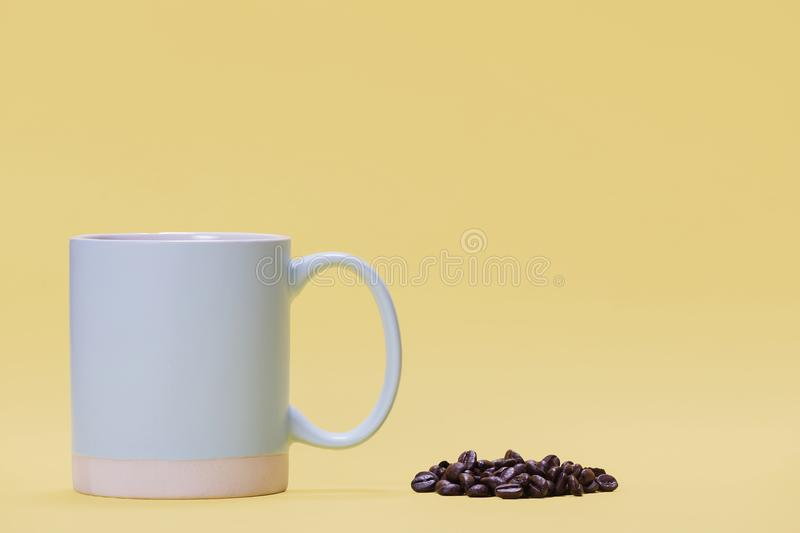 Blue coffee cup next to a pile of beans on yellow. Blue coffee cup next to a pile of coffee beans on a bright yellow background royalty free stock images