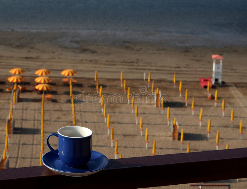 Blue coffee cup over an italian beach. With beach umbrellas and lifeguard tower royalty free stock photo
