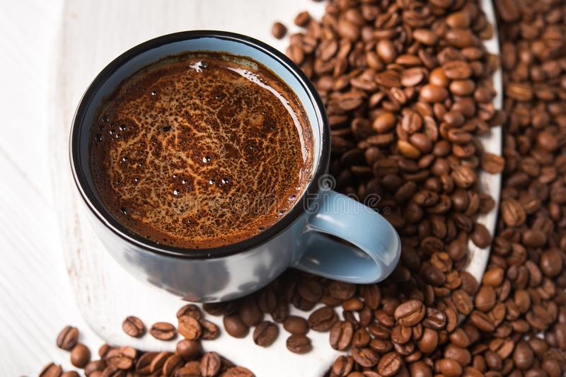 Blue coffee cup with roasted beans. On a wooden table stock images