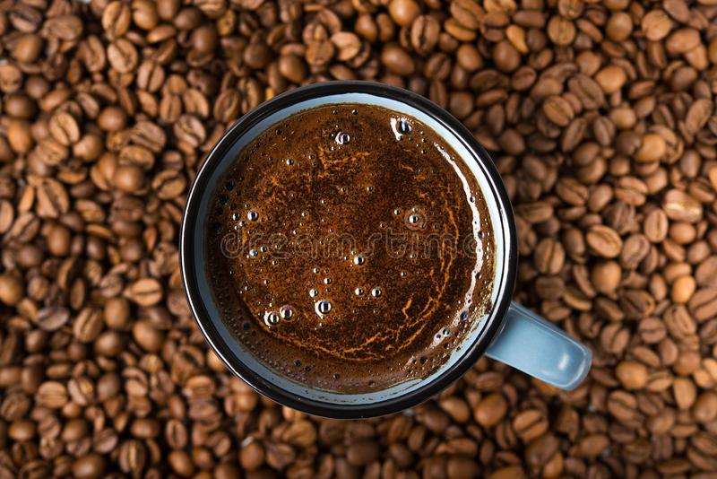 Blue coffee cup with roasted beans. On a wooden table. top view royalty free stock image