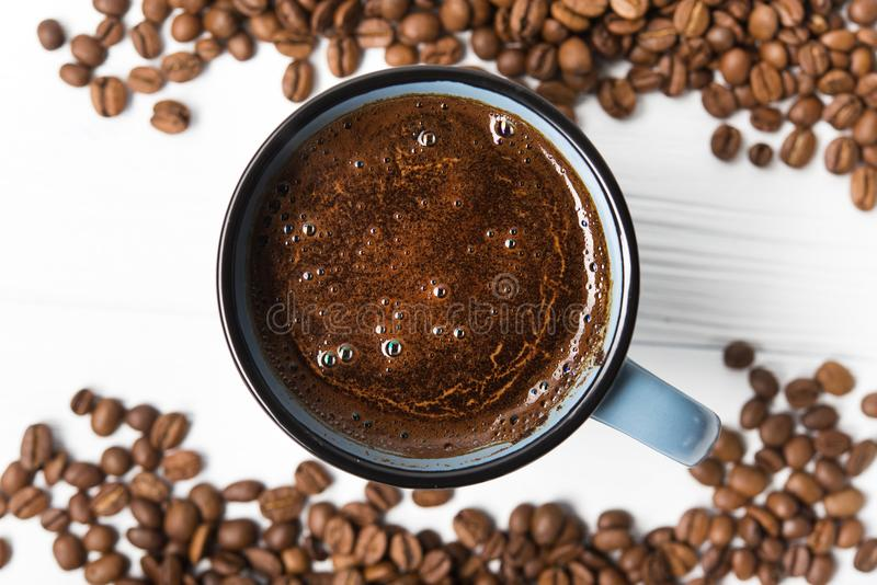 Blue coffee cup with roasted beans. On a wooden table. top view stock photography