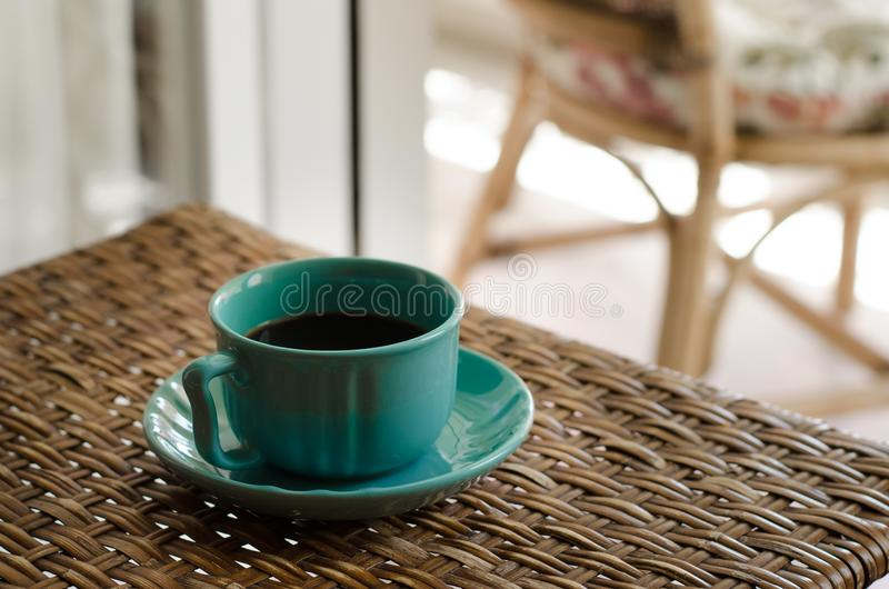Blue Coffee Cup With Saucer Filled With Coffee on Top of Wicker Table royalty free stock photos