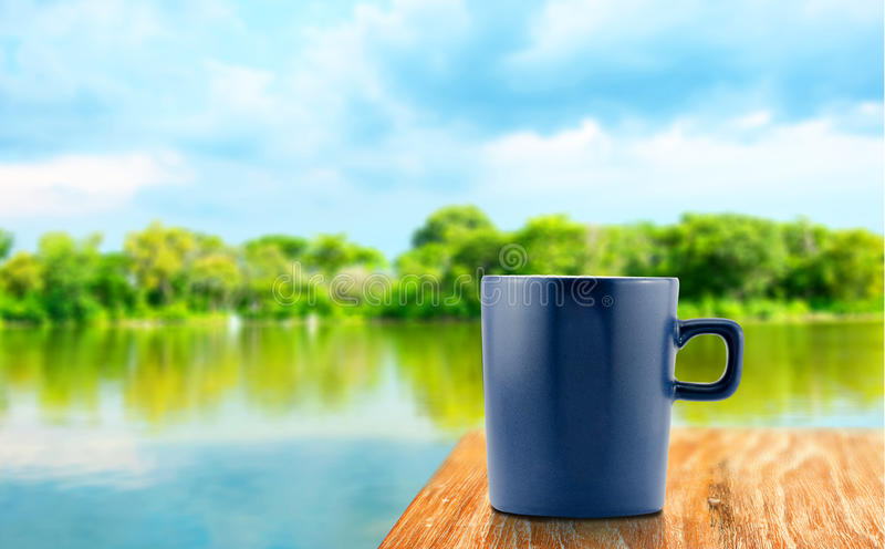 Blue Coffee cup on wood table at blur tree and lagoon background.  royalty free stock images