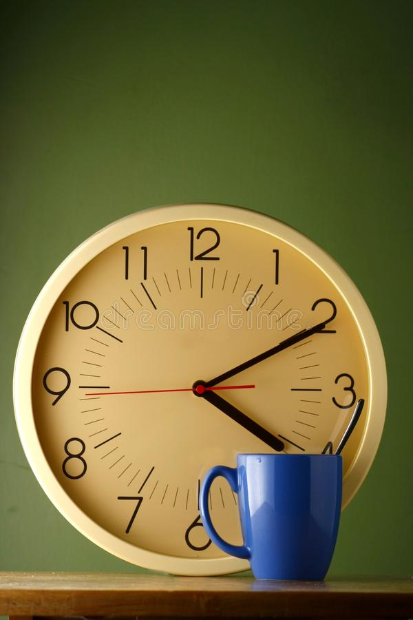 Blue coffee mug and an analog clock. Blue coffee mug with a teaspoon and an analog clock stock images