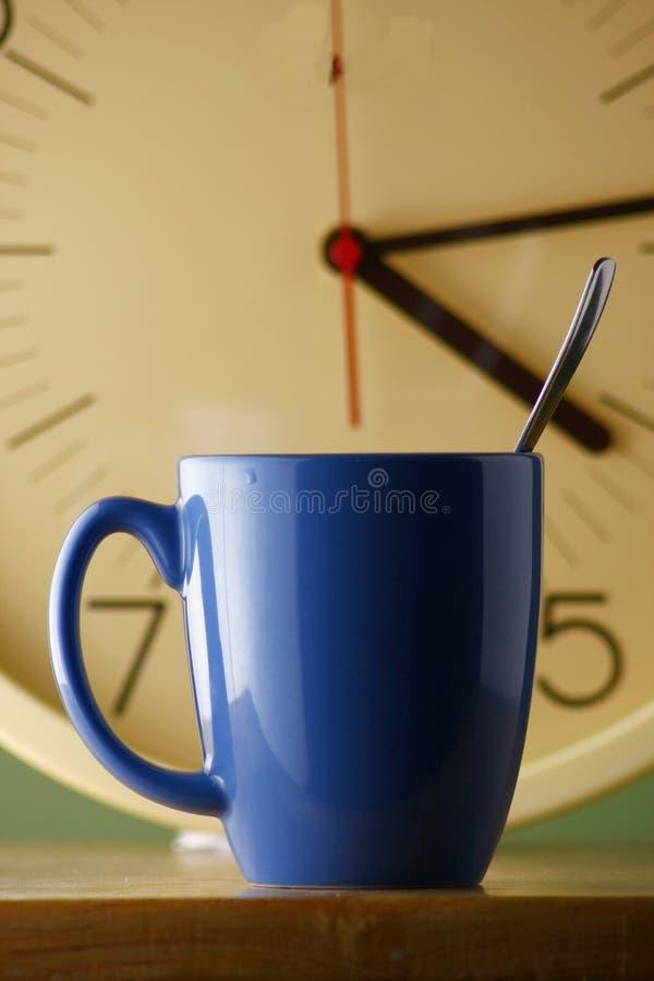 Blue coffee mug and an analog clock. Blue coffee mug with a teaspoon and an analog clock royalty free stock images