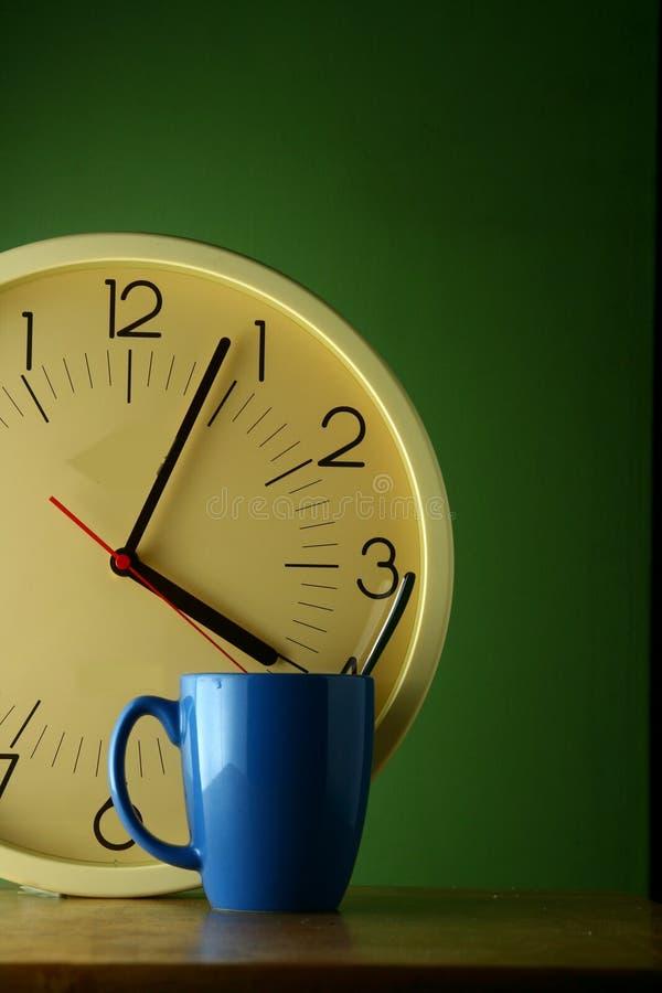 Blue coffee mug and an analog clock. Blue coffee mug with a teaspoon and an analog clock stock photo
