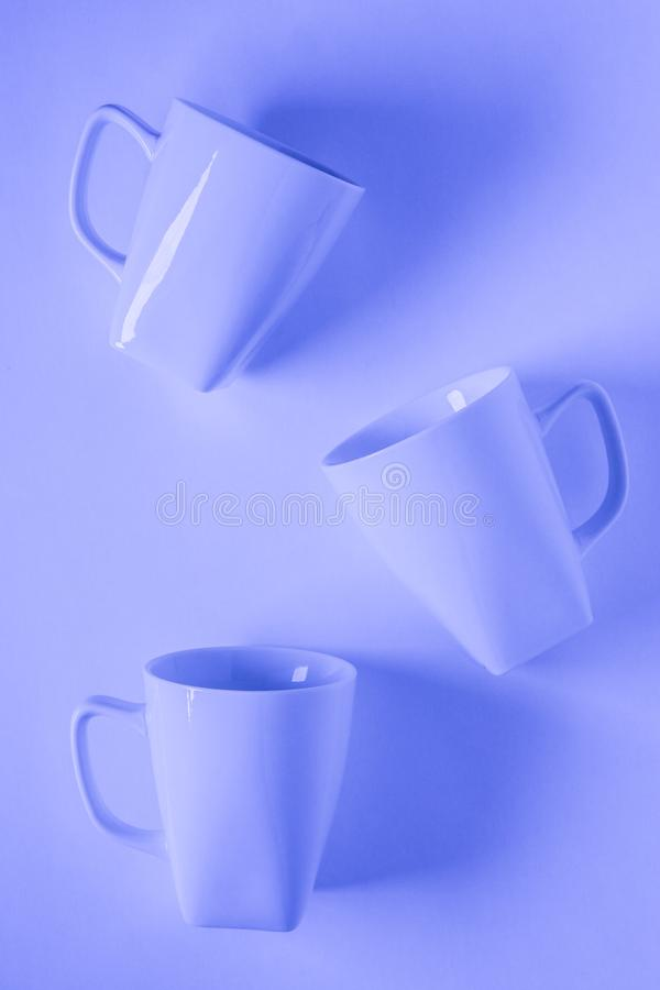 3 blue coffee mugs on blue background scattered with empty copyspace. 3 monochromatic blue coffee mugs scattered on blue background with blank empty room space royalty free stock photography