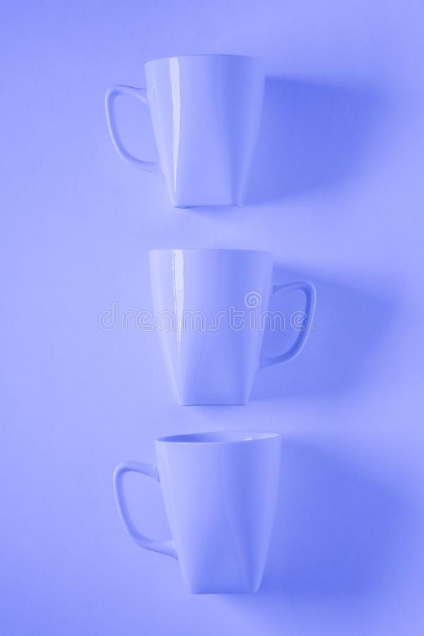 3 blue coffee mugs on blue background in a vertical row with empty copyspace. 3 monochromatic blue coffee mugs lined up in a row on blue background with blank royalty free stock images